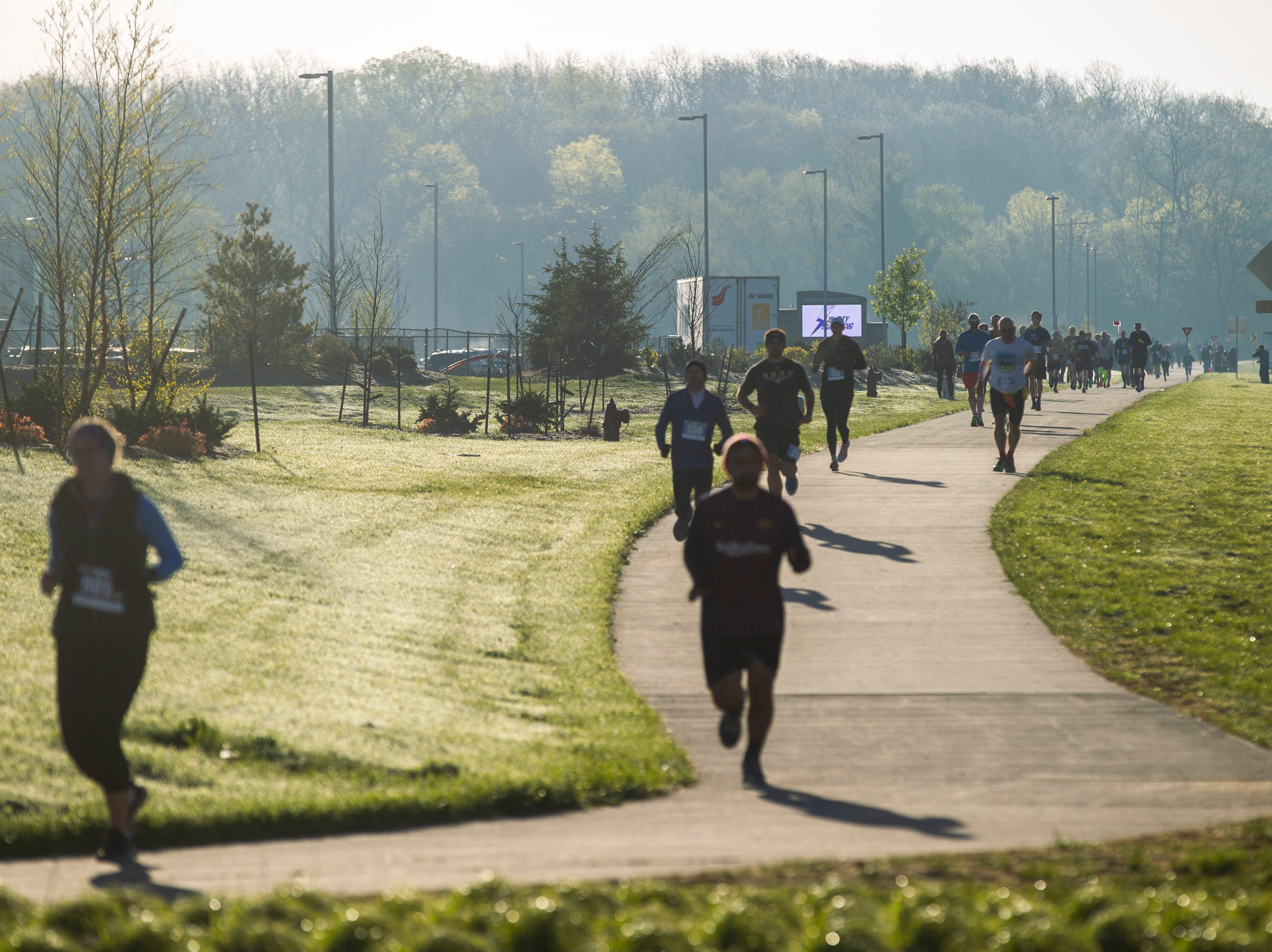 Runners pass Liberty High School during the second annual Run CRANDIC marathon, Sunday, April 28, 2019, along Dubuque Street in North Liberty, Iowa.