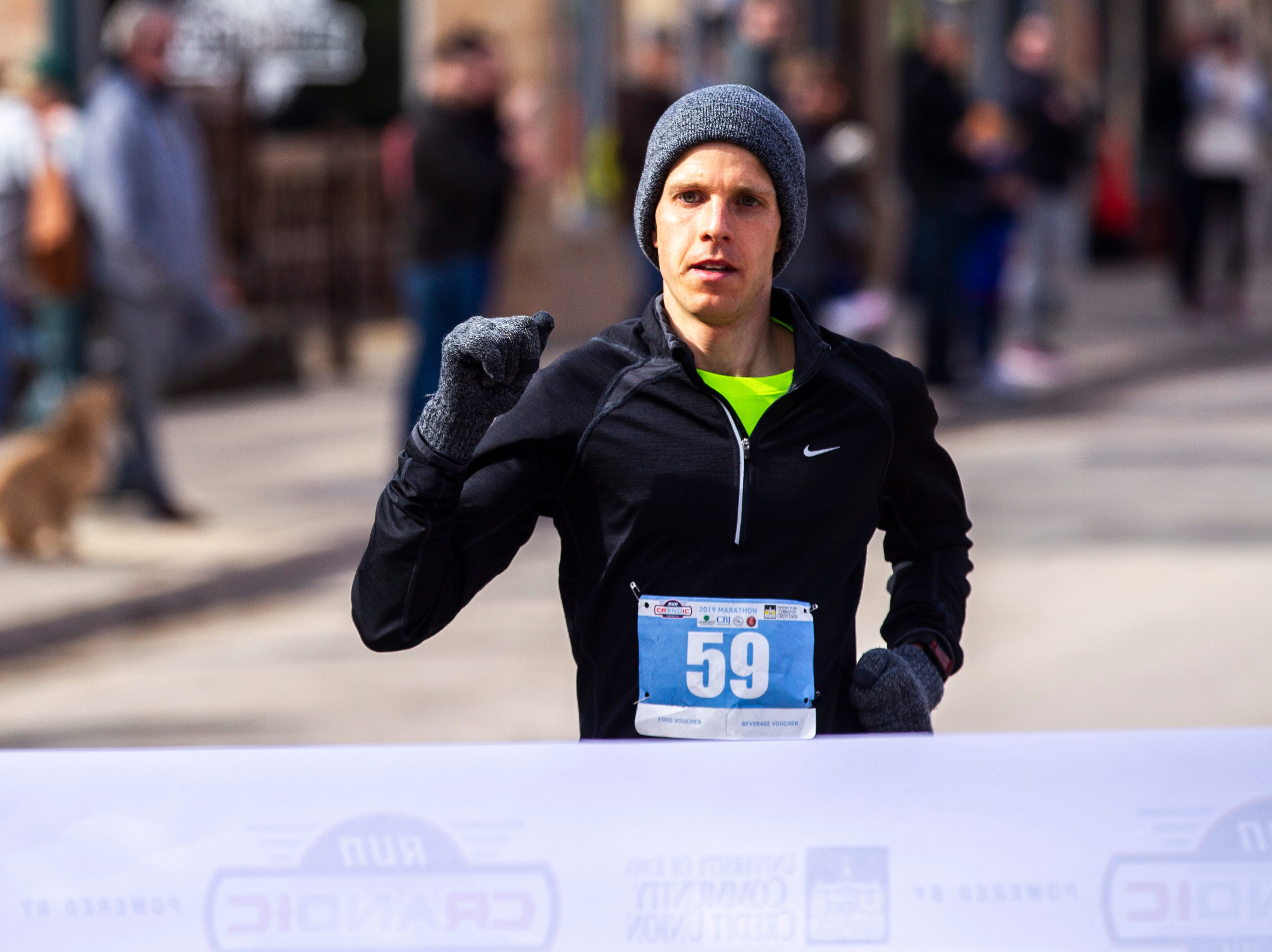 Tyler Culver of Cedar Rapids celebrates while crossing the finish line to be the first man to finish during the second annual Run CRANDIC marathon, Sunday, April 28, 2019, along 16th Avenue SE in Cedar Rapids, Iowa. Culver finished with a time of 2:50:02.