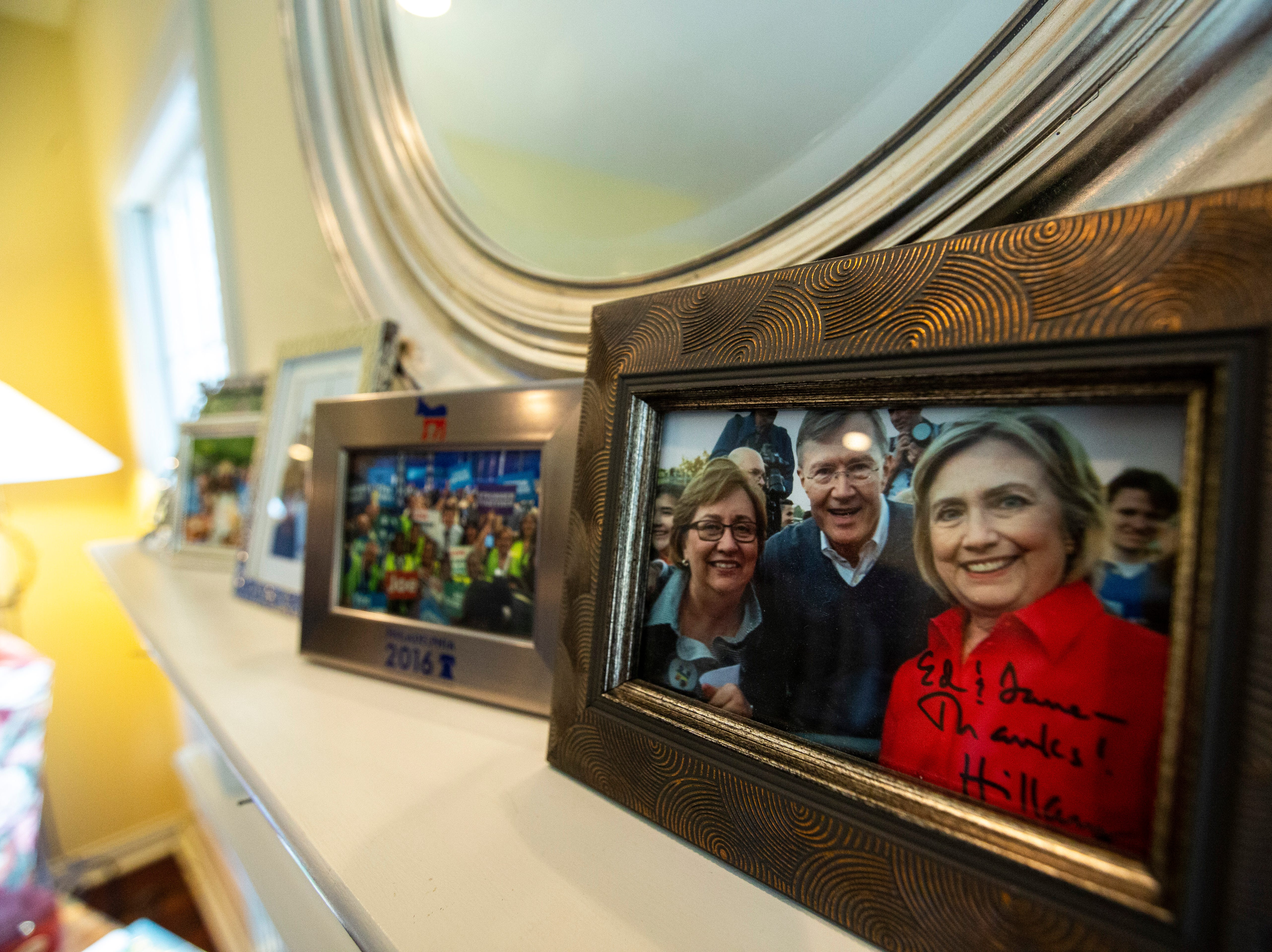 """A framed photo of Ed and Jane Cranston with Hillary Clinton sits on a shelf at a house party hosted by the """"Potluck Insurgency"""" group, Sunday, April 28, 2019, at a home in North Liberty, Iowa."""