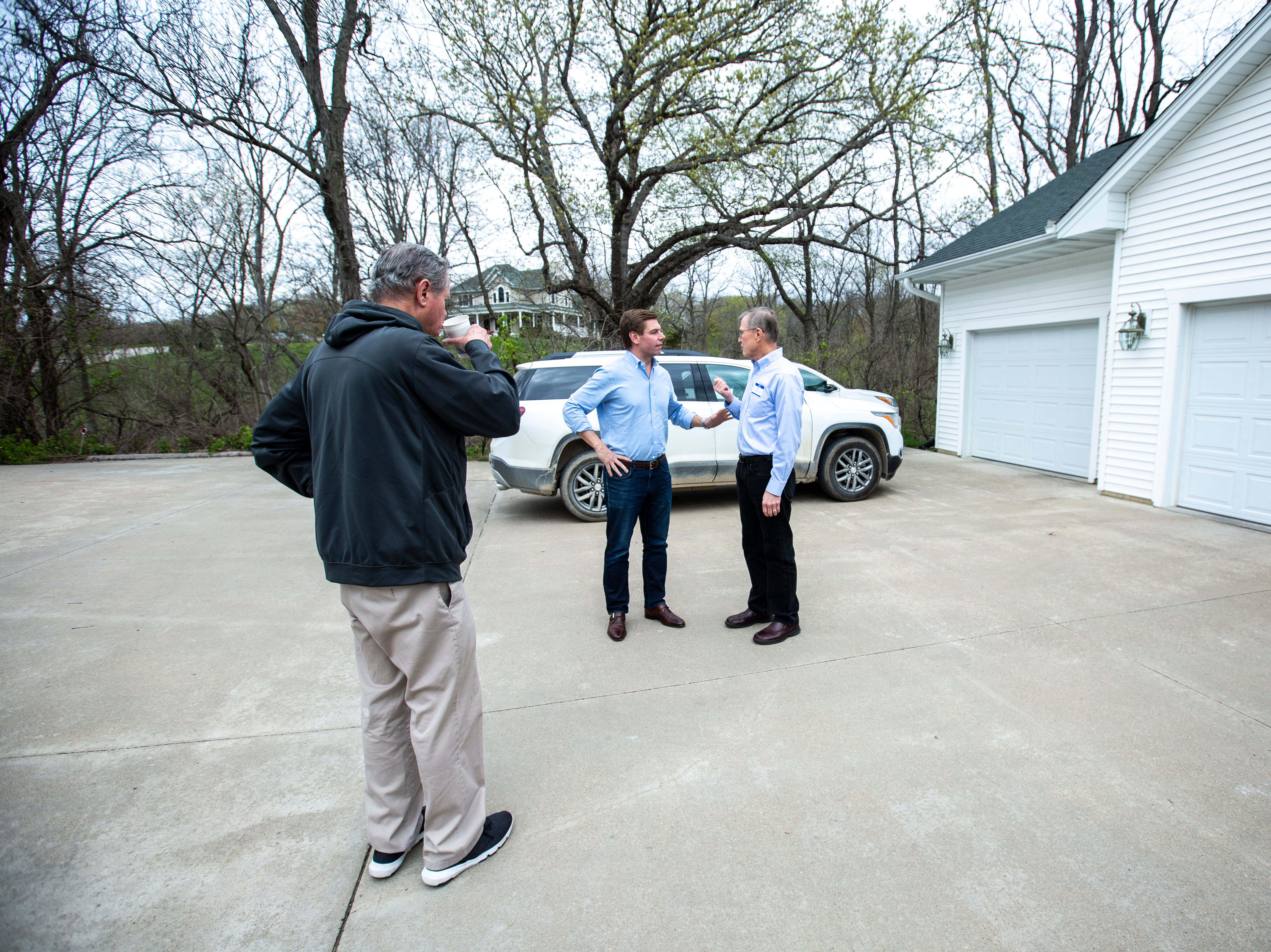 """U.S. Rep. Eric Swalwell, D-Calif., talks with Ed Cranston, right, before speaking to a group at a house party hosted by the """"Potluck Insurgency"""" group, Sunday, April 28, 2019, at a home in North Liberty, Iowa."""