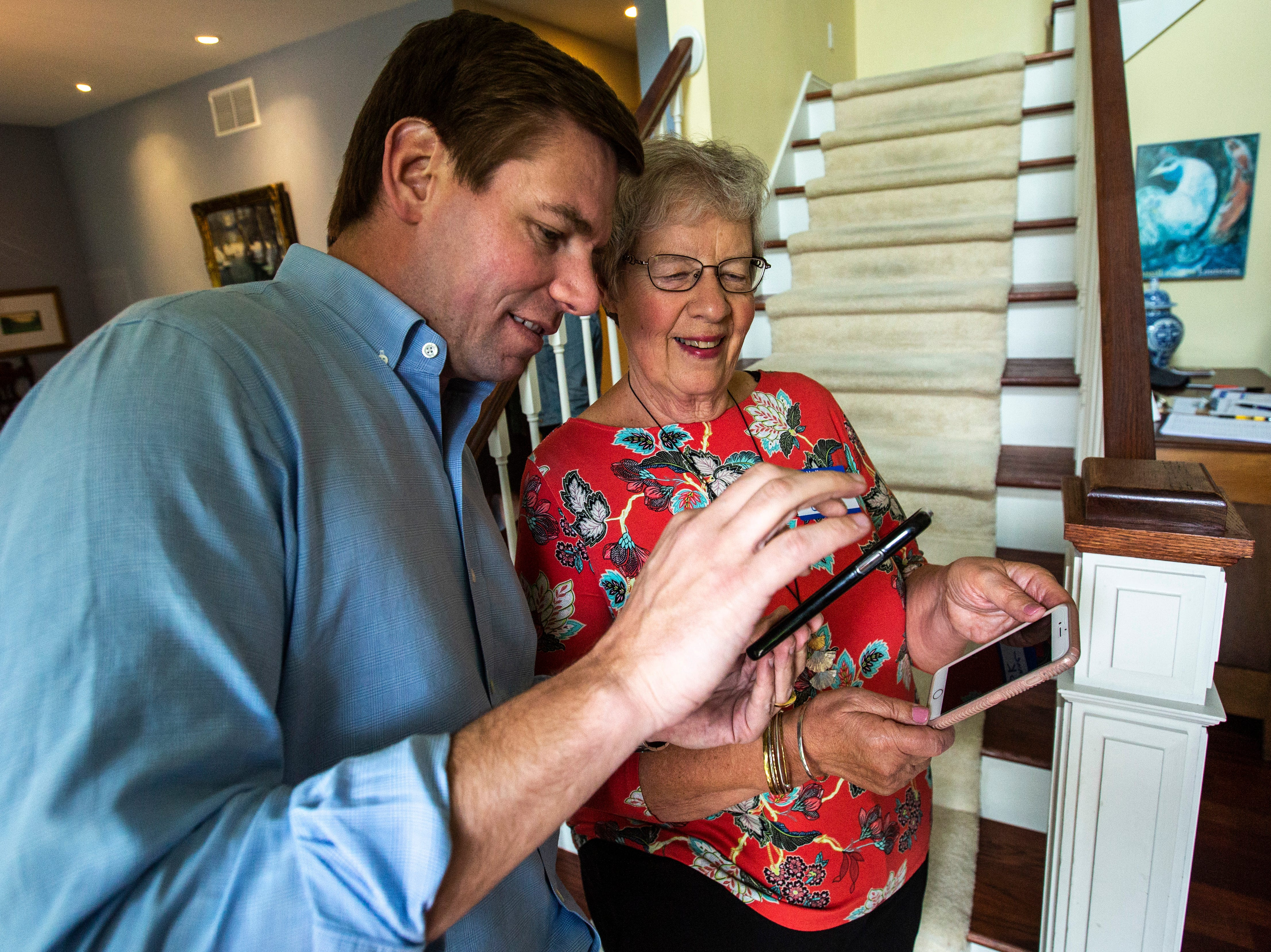 """U.S. Rep. Eric Swalwell, D-Calif., pulls up photos of his children to show Rosanne Cook while arriving at a house party hosted by the """"Potluck Insurgency"""" group, Sunday, April 28, 2019, at a home in North Liberty, Iowa."""