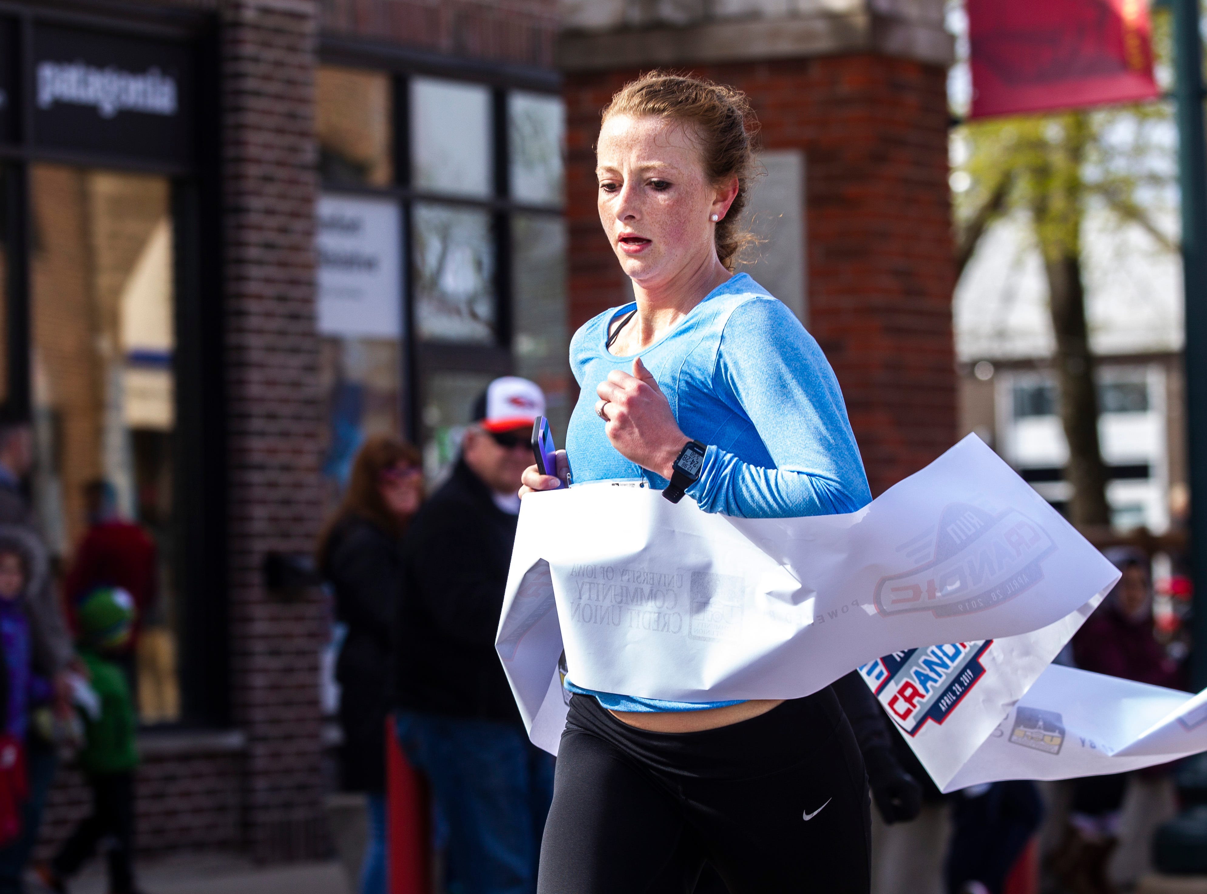Regan Weidner crosses the finish line to be the first woman to finish the half marathon during the second annual Run CRANDIC marathon, Sunday, April 28, 2019, along 16th Avenue SE in Cedar Rapids, Iowa. Weidner finished with a time of 1:24:26.