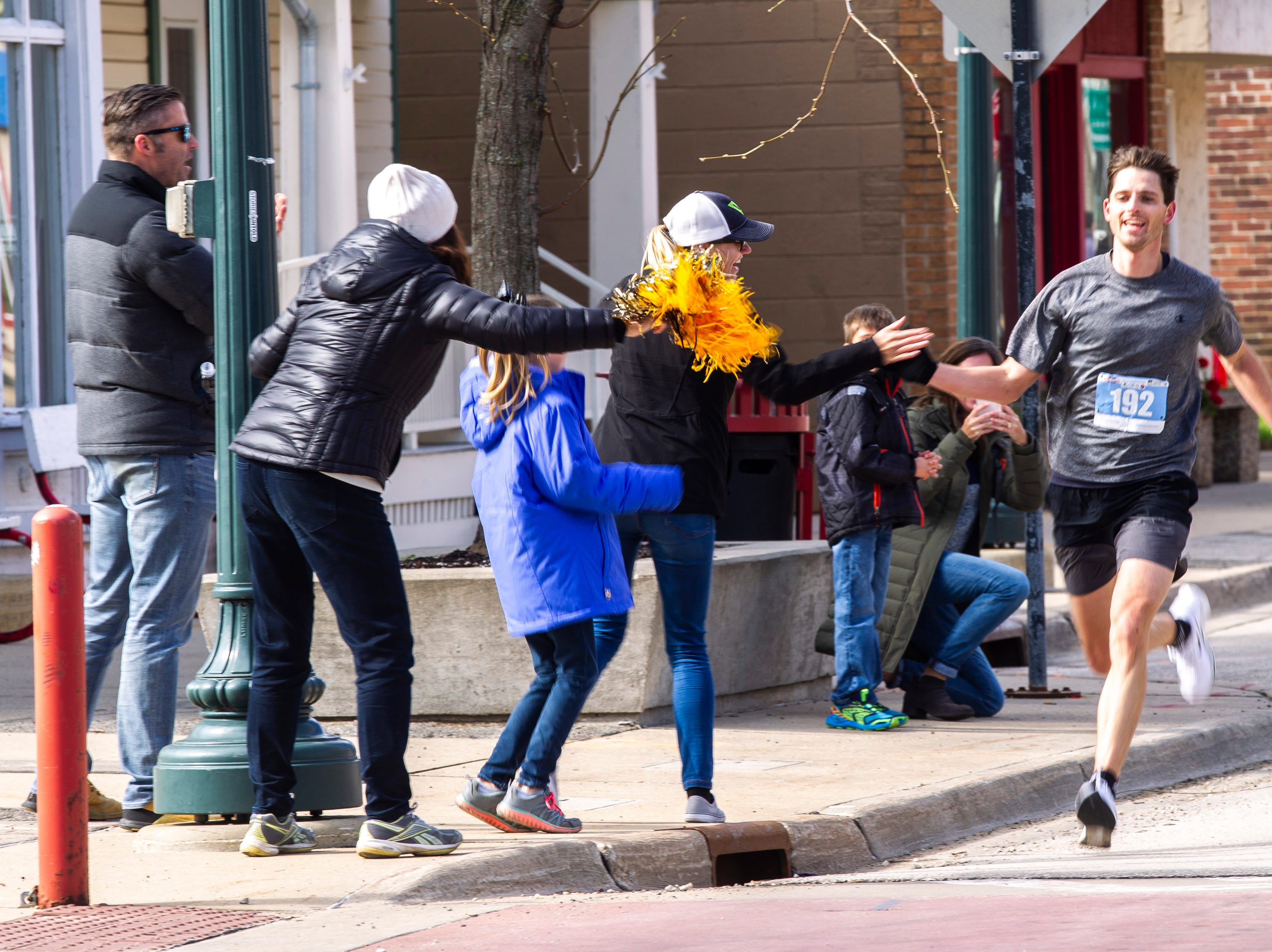 Joshua Lawrence gets a high-five from supporters while nearing the finish line during the second annual Run CRANDIC marathon, Sunday, April 28, 2019, along 16th Avenue SE in Cedar Rapids, Iowa.