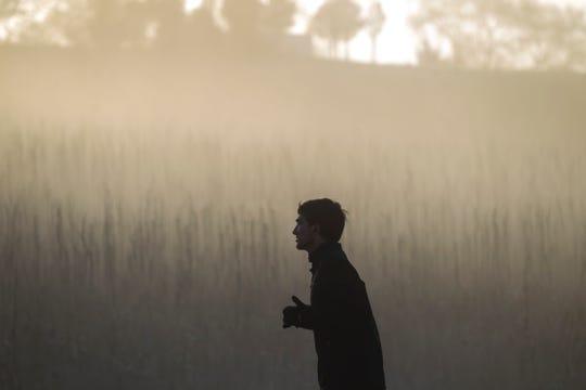 A runner ascends a hill as sun shines through a foggy valley during the second annual Run CRANDIC marathon, Sunday, April 28, 2019, along Dubuque Street in Iowa City, Iowa.
