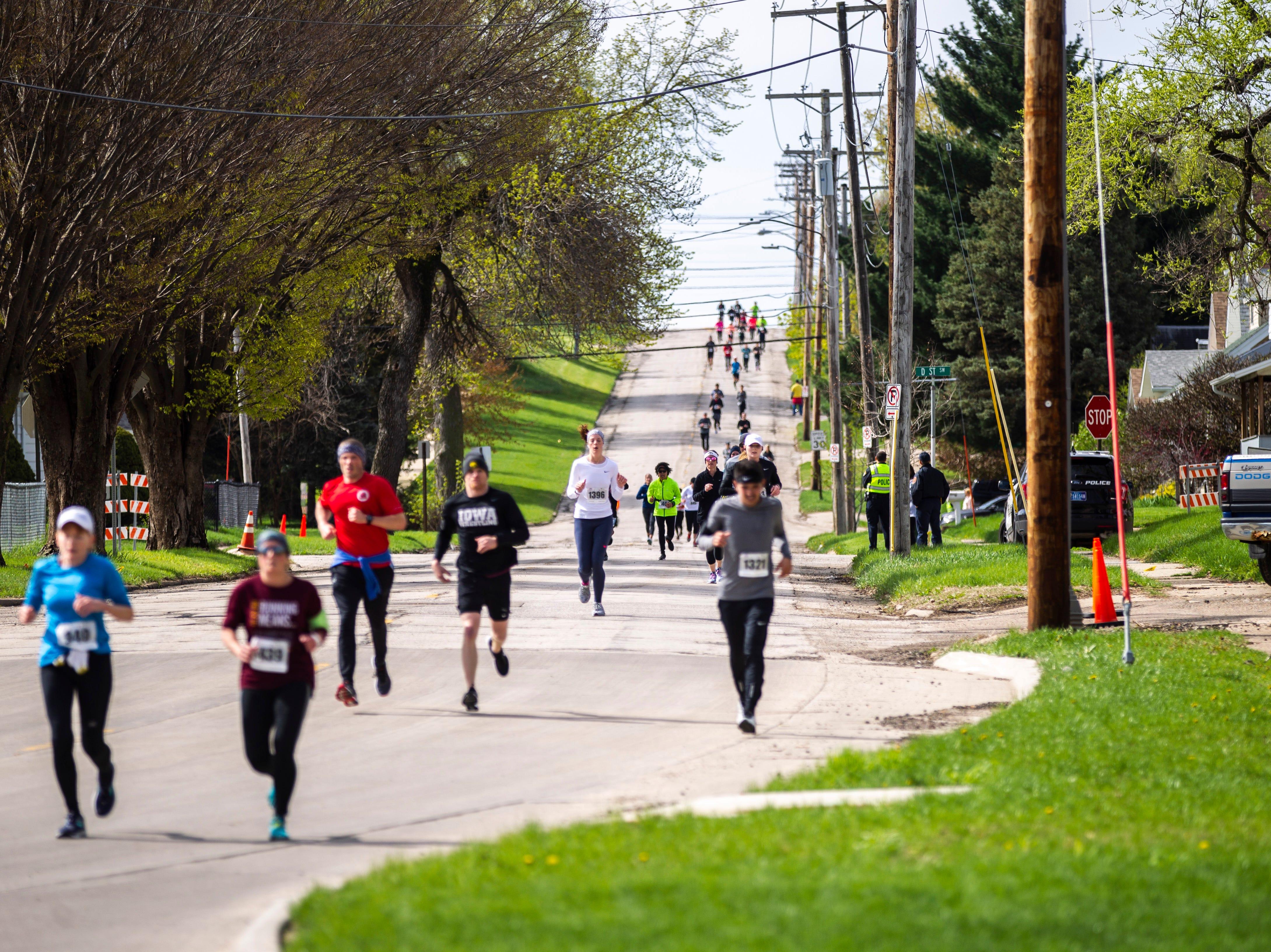Runners near the 26 mile mark during the second annual Run CRANDIC marathon, Sunday, April 28, 2019, along Bowling Street SW in Cedar Rapids, Iowa.