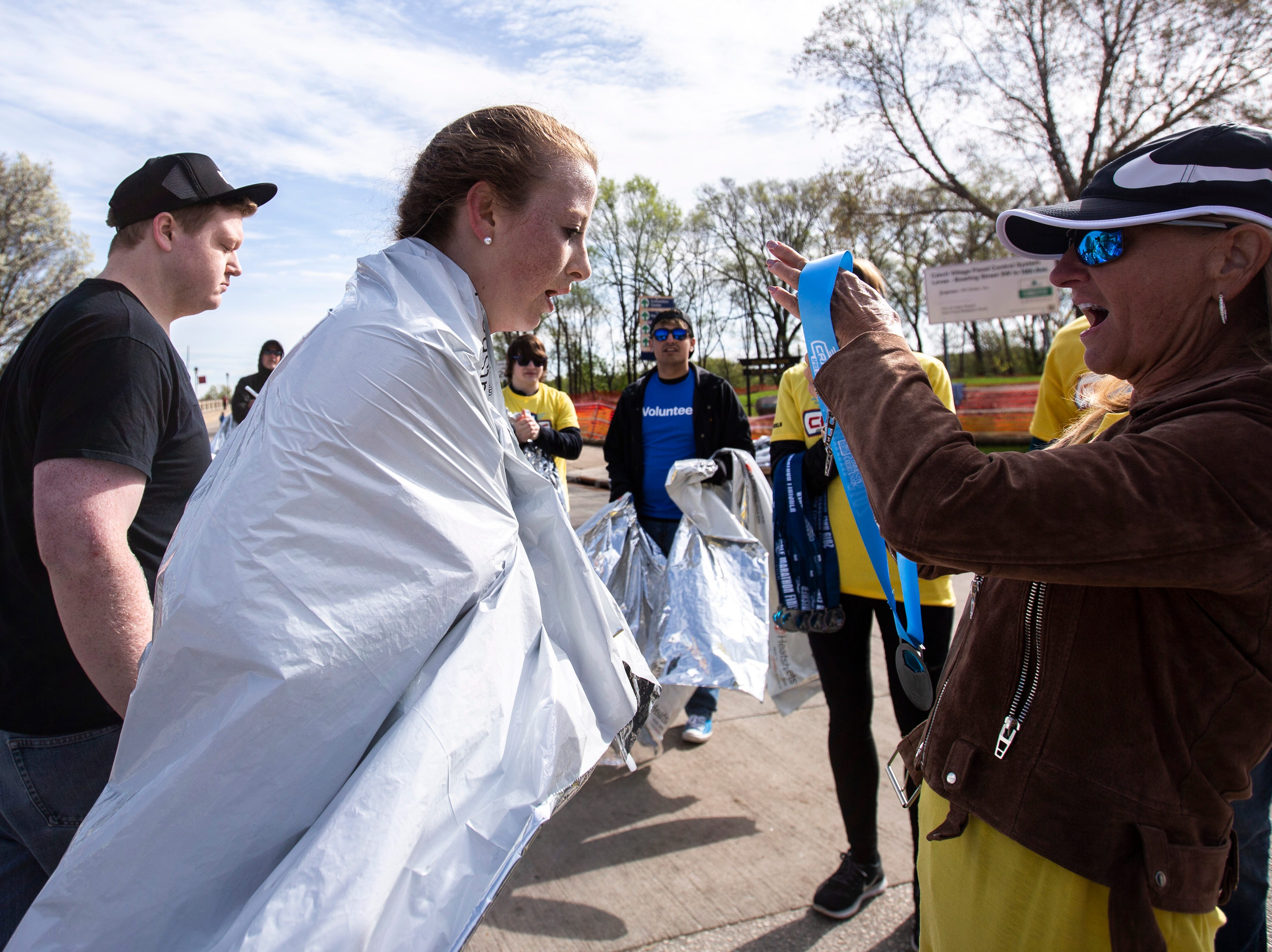 Regan Weidner receives a medal past the finish line after being the first woman to finish the half marathon during the second annual Run CRANDIC marathon, Sunday, April 28, 2019, along 16th Avenue SE in Cedar Rapids, Iowa. Weidner finished with a time of 1:24:26.
