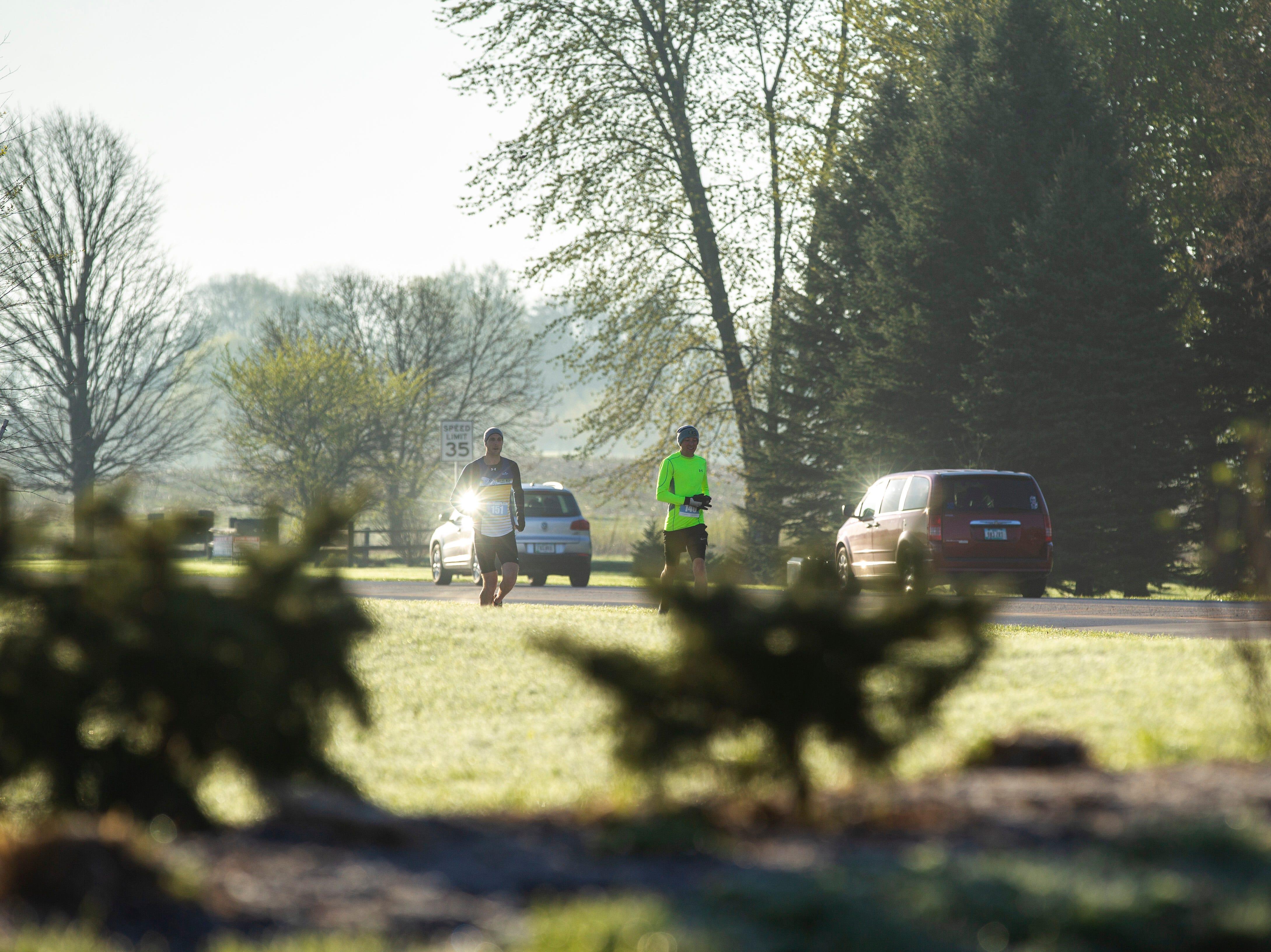 Tad Hulst, left, and Derek Henscheid run during the second annual Run CRANDIC marathon, Sunday, April 28, 2019, along Dubuque Street in North Liberty, Iowa.