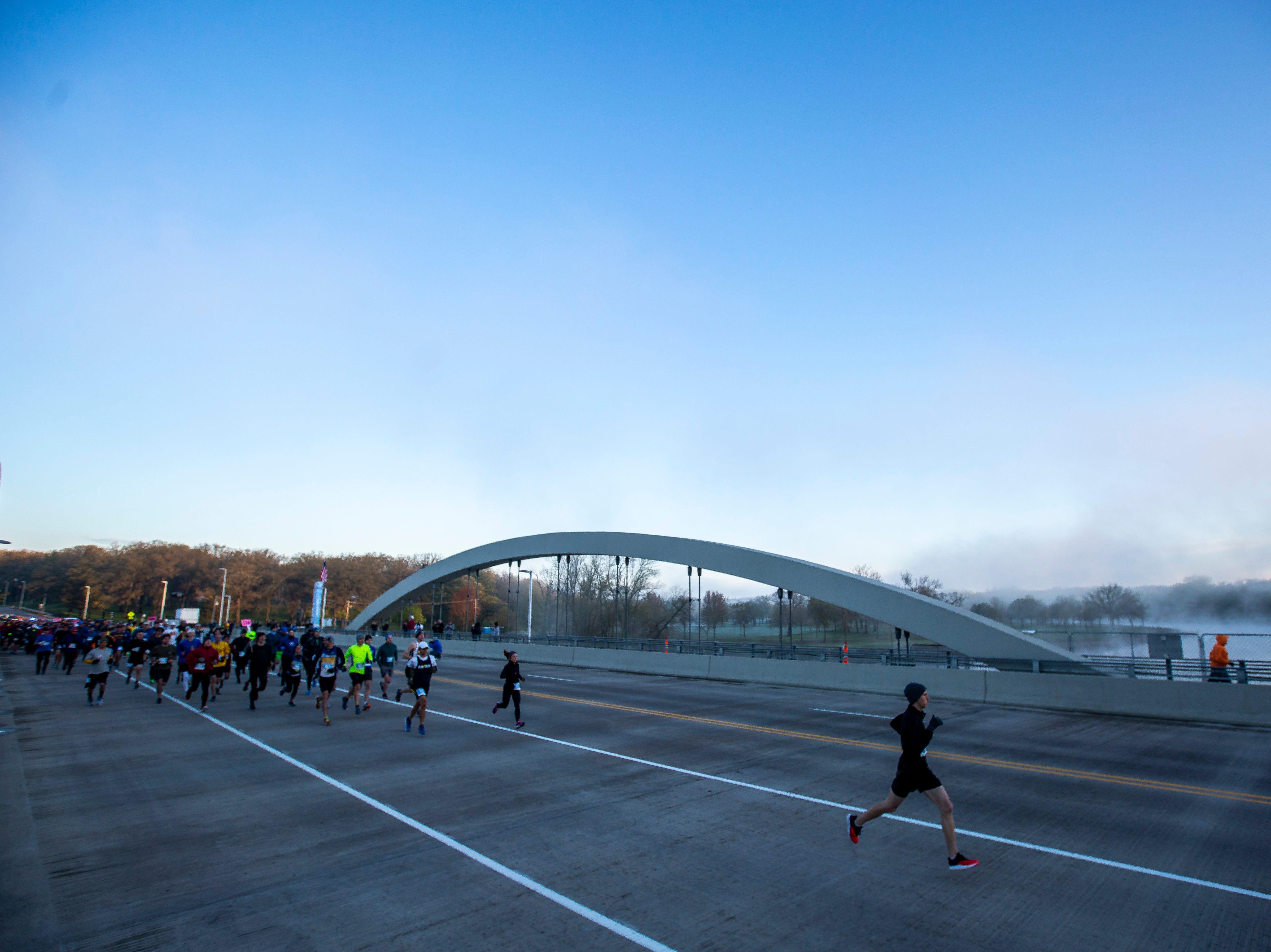 Runners break away at the start during the second annual Run CRANDIC marathon, Sunday, April 28, 2019, across the Park Street Road Bridge over the Iowa River in Iowa City, Iowa.