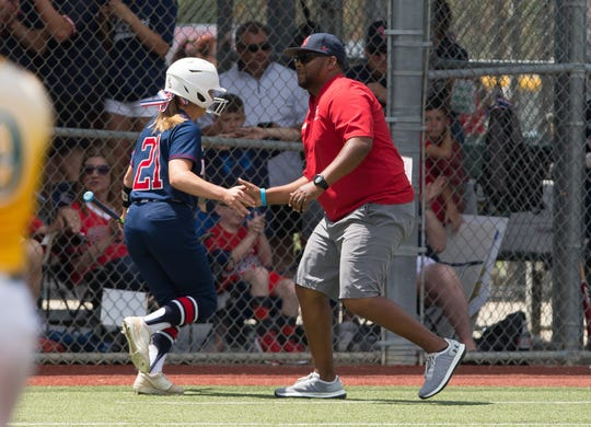Notre Dame's Amy Daigle is greeted by coach Dale Serie as the Lady Pios play Holy Savior Menard in the LHSAA Division III softball state championship Saturday.