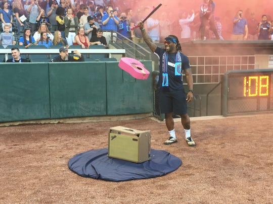University of Memphis football legend and former NFL running back DeAngelo Williams holds the remnants of a guitar he smashed on April 27, 2018 before the Memphis 901 FC soccer game against the Charleston Battery at AutoZone Park.