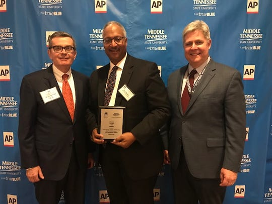 Commercial Appeal Executive Editor Mark Russell, center, accepts an award on behalf of the newspaper.