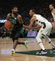 Boston Celtics guard Kyrie Irving turns the corner past Bucks guard George Hill. Irving had 26 points and 11 assists.