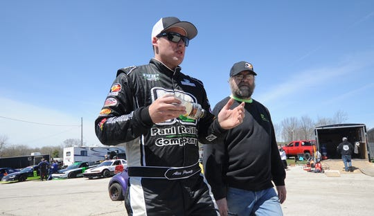 Reigning super-late model champion Alex Prunty and his father, Dan, walk through the pits during opening day at Slinger Speedway on Sunday.