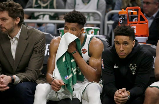 A dejected Giannis Antetokounmpo sits on the bench next to Bucks teammate Malcolm Brogdon in the closing minutes of the fourth quarter Sunday.