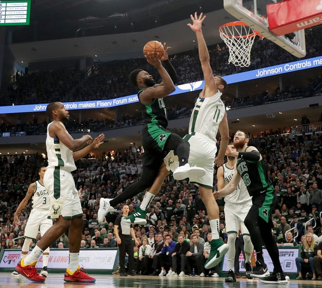 Celtics guard Jaylen Brown shoots over Milwaukee Bucks center Brook Lopez Sunday.