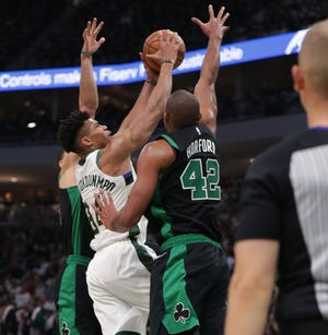 Bucks forward Giannis Antetokounmpo has his shot blocked by Celtics center Al Horford Sunday.