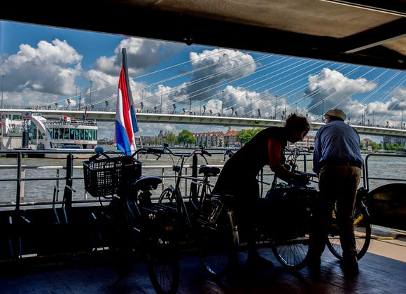 Bikers put their bikes on a waterbus in Rotterdam, heading towards Kinderdijk
