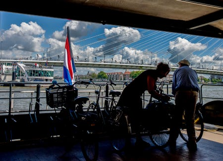 Bikers put their bikes on a waterbus in Rotterdam, heading towards Kinderdijk