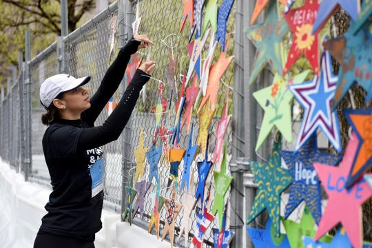 Jofeliny Franco of Queens, secures a Star of HOPE to the construction fence surrounding the 9/11 Memorial Glade on April 28, 2019. Franco lost her uncle on 9/11. The stars will be presented to 9/11 first responders, family members, health advocates and others during the Glade dedication May 30, 2019, the 17th anniversary of the official end of the recovery mission at Ground Zero.
