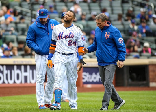 New York Mets second baseman Robinson Cano (24) is taken out of the game after getting hit by a pitch in the first inning against the Milwaukee Brewers at Citi Field.