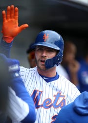 New York Mets first baseman Pete Alonso (20) celebrates with teammates in the dugout after scoring a run in the first inning against the Milwaukee Brewers at Citi Field.