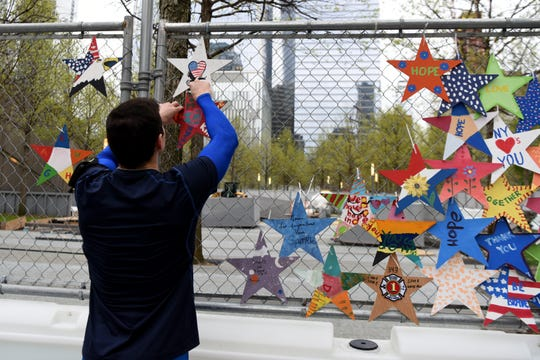 Mark LaPointe, 25 of Manhattan, secures a Star of HOPE to the construction fence surrounding the 9/11 Memorial Glade on April 28, 2019. The stars will be presented to 9/11 first responders, family members, health advocates and others during the Glade dedication May 30, 2019, the 17th anniversary of the official end of the recovery mission at Ground Zero.