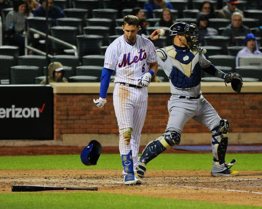 Apr 27, 2019; New York City, NY, USA; New York Mets second baseman Jeff McNeil (6) reacts by throwing his helmet after striking out with two men on base against the Milwaukee Bucks during the eighth inning at Citi Field.