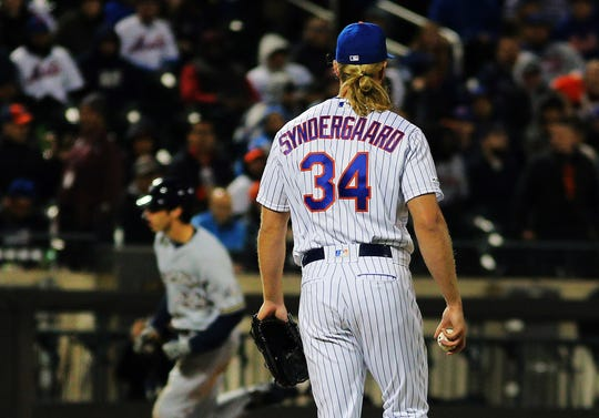 Apr 27, 2019; New York City, NY, USA; New York Mets starting pitcher Noah Syndergaard (34) looks on as Milwaukee Brewers right fielder Christian Yelich (22) rounds the bases after hitting a solo home run against the New York Mets during the fourth inning at Citi Field.