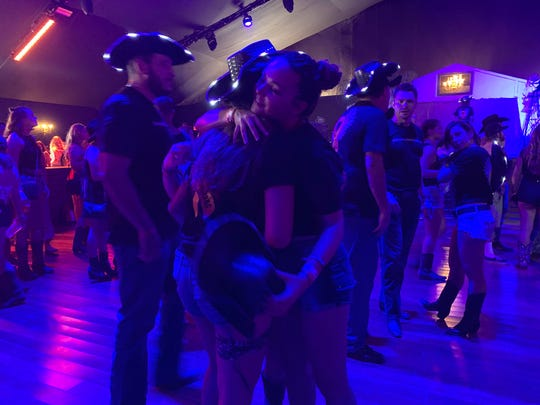 """People hug after Honey Country performs """"Country Strong"""" in the Honky Tonk Dance Hall during the Stagecoach country music festival in Indio, Calif., on April 27, 2019."""
