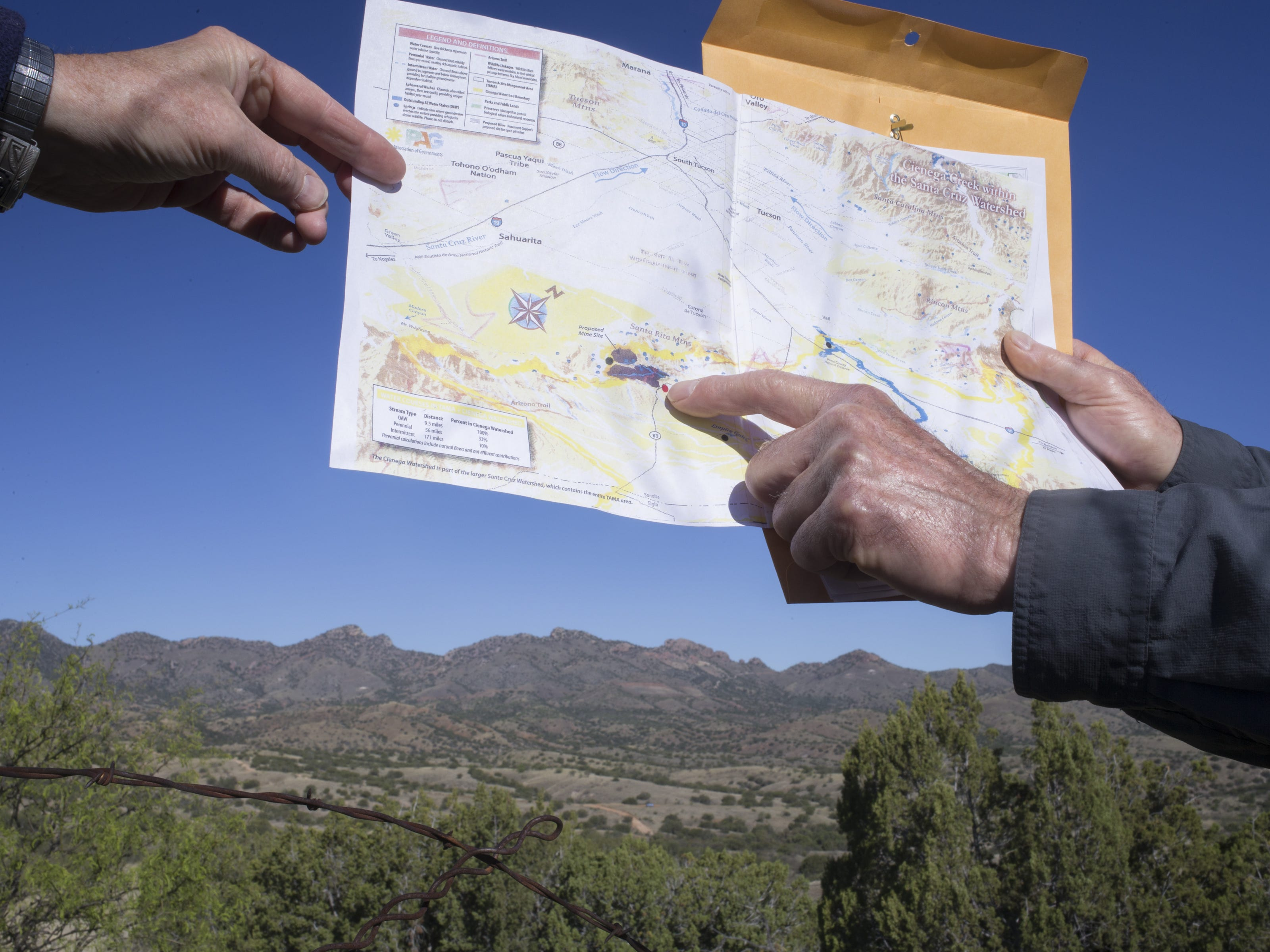 Vice President of Save the Scenic Santa Ritas Greg Shinsky (right) points to his location on a map, April 24, 2019. The gray area to the left on the map is the proposed Rosemont Mine site.