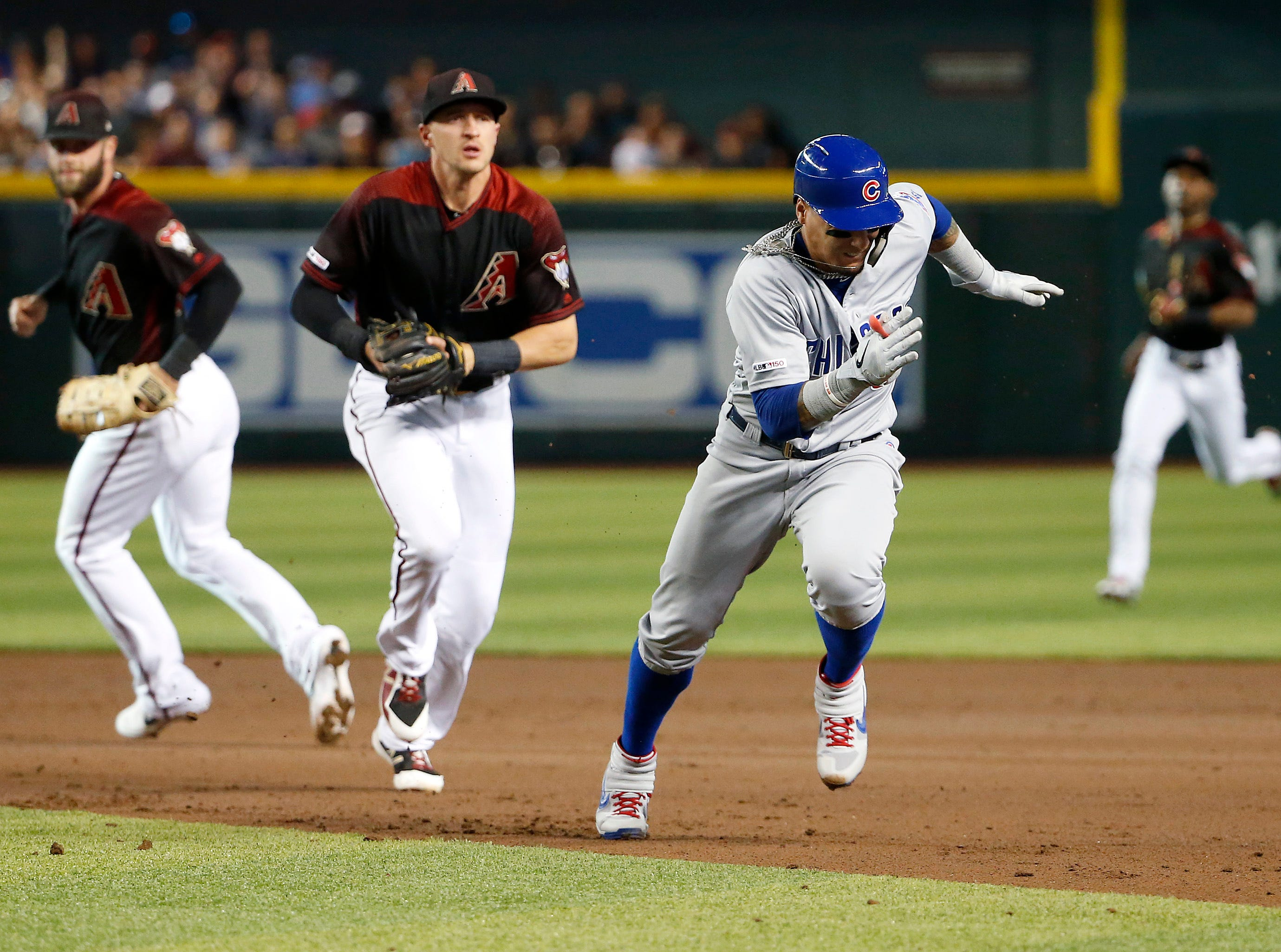 Chicago Cubs' Javier Baez, right, is chased by Arizona Diamondbacks shortstop Nick Ahmed, center, as he gets caught in a run-down during the second inning of a baseball game, Saturday, April 27, 2019, in Phoenix. Baez was out on the play. (AP Photo/Ralph Freso)