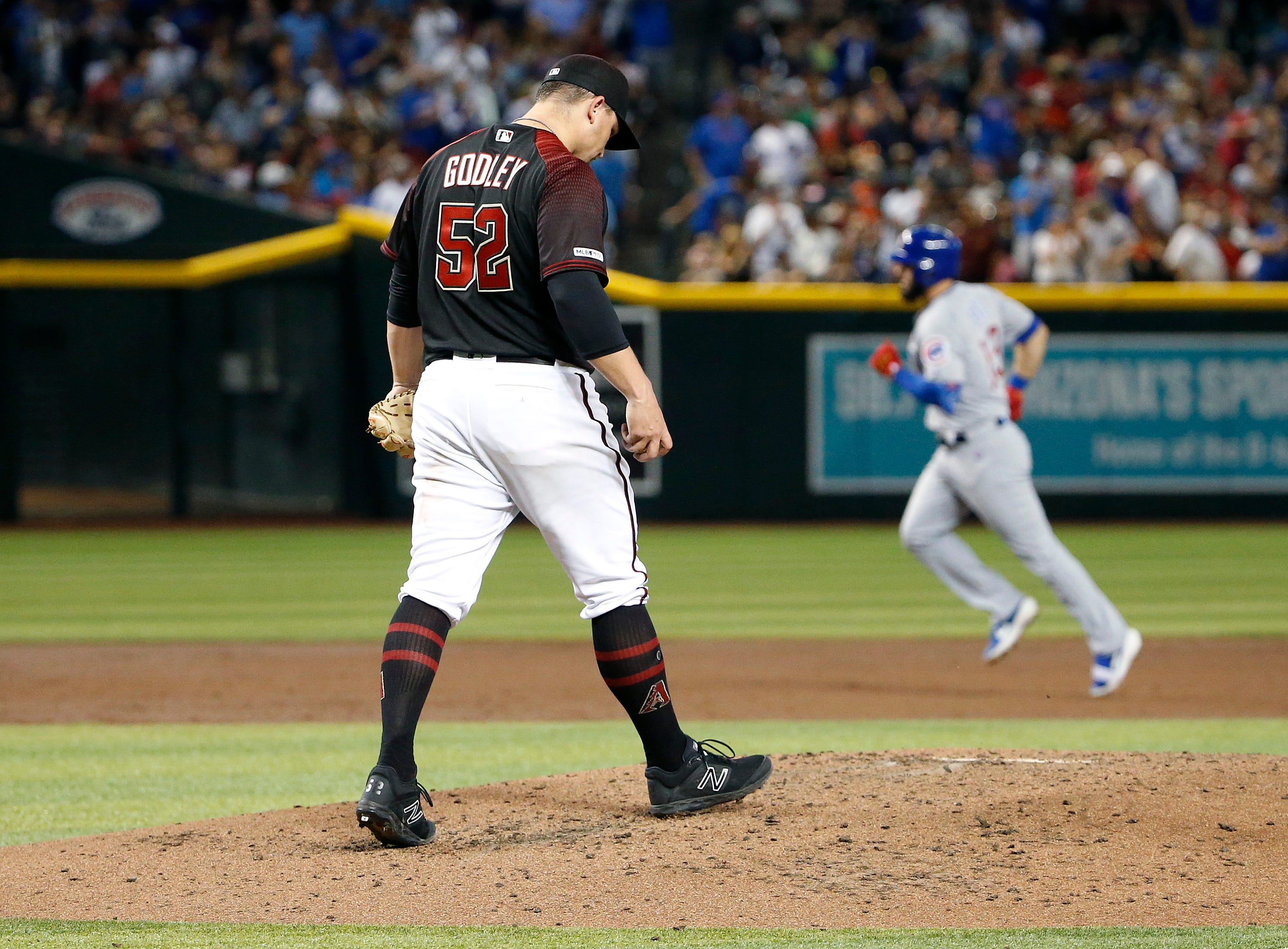 Arizona Diamondbacks starting pitcher Zack Godley (52) walks back to the mound after giving up a three-run home run to Chicago Cubs' David Bote, right, during the third inning of a baseball game, Saturday, April 27, 2019, in Phoenix. (AP Photo/Ralph Freso)