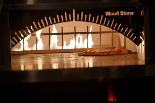 A pizza bakes inside a stone oven in the 1580 Lounge at The Orchards in Chambersburg on April 23, 2019.