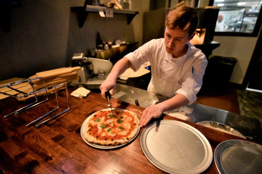 Chef Kolton Regi slices a fresh-out-of-the-oven pizza on April 23, 2019, in the open kitchen of the new 1580 Lounge at The Orchards, 1580 Orchard Drive, Chambersburg.