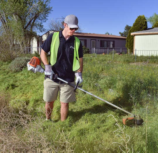 Ben Mollman, plant manager at Polaris, knocks down brush with a weed eater near the Fernley roundabout.