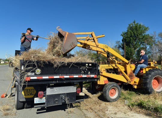 Greg Garvin, on truck bed, helps empty brush from Dana Uhlhorn's tractor scoop at Ponderosa Park.