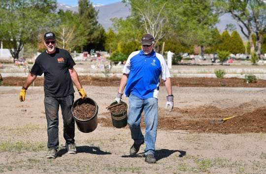 Pioneer Crossing General Manager George Owens (left) and Fernley Free Methodist Church Pastor Mike Moresi carry mulch to spread around plantings at Desert Memorial Garden Cemetery.