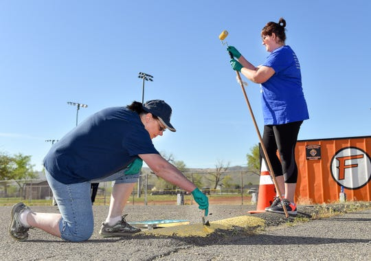 Molly Tomb paints a speed bump at Out of Town Park as her daughter DeAnna Tomb prepares a paint roller.