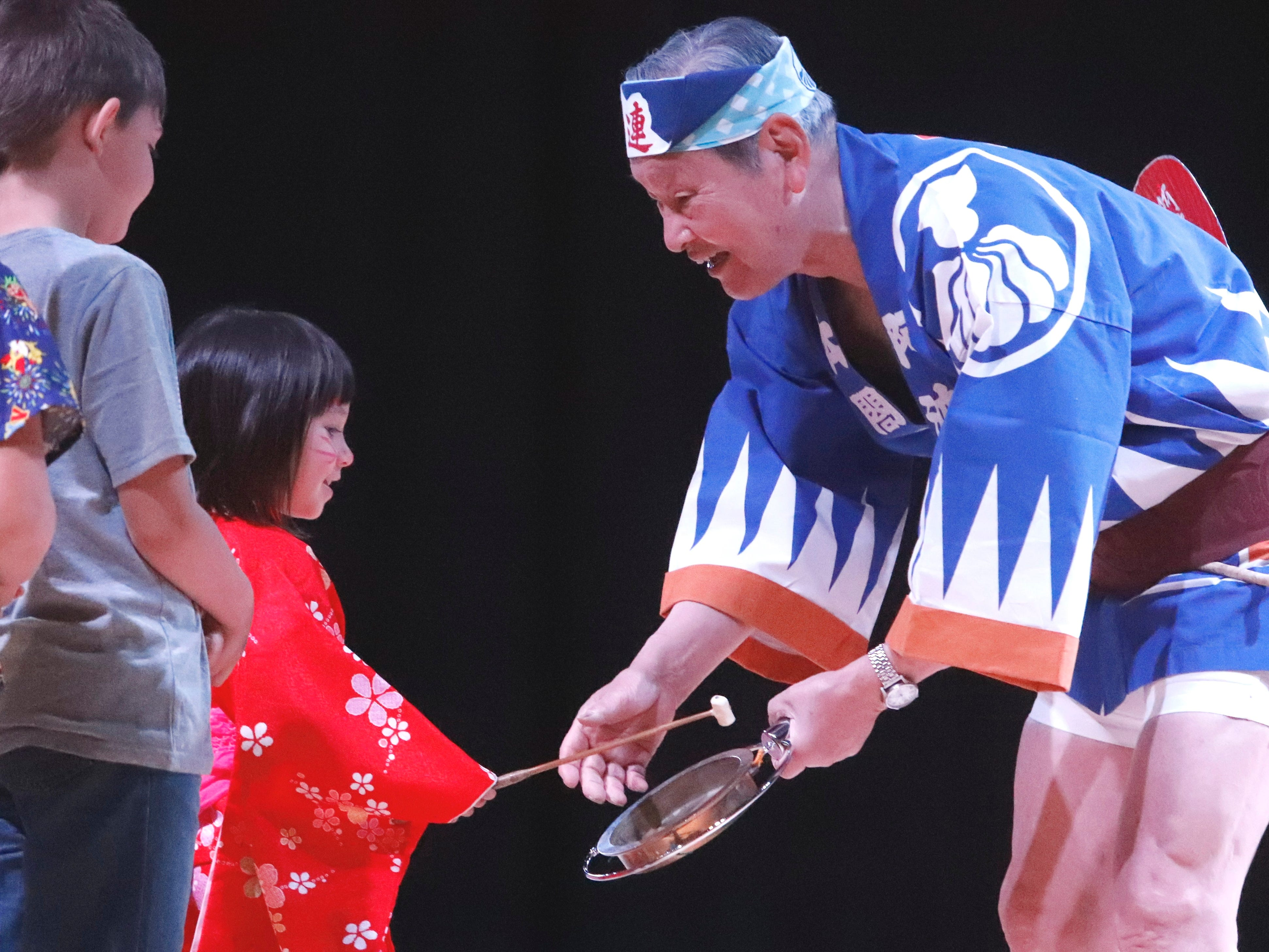 An Owa-Odori performer lets a child play  the kane (small gong) on stage Saturday, April 27, 2019, during 2019 Cherry Blossom Festival at Sequoia Middle School in Redding.