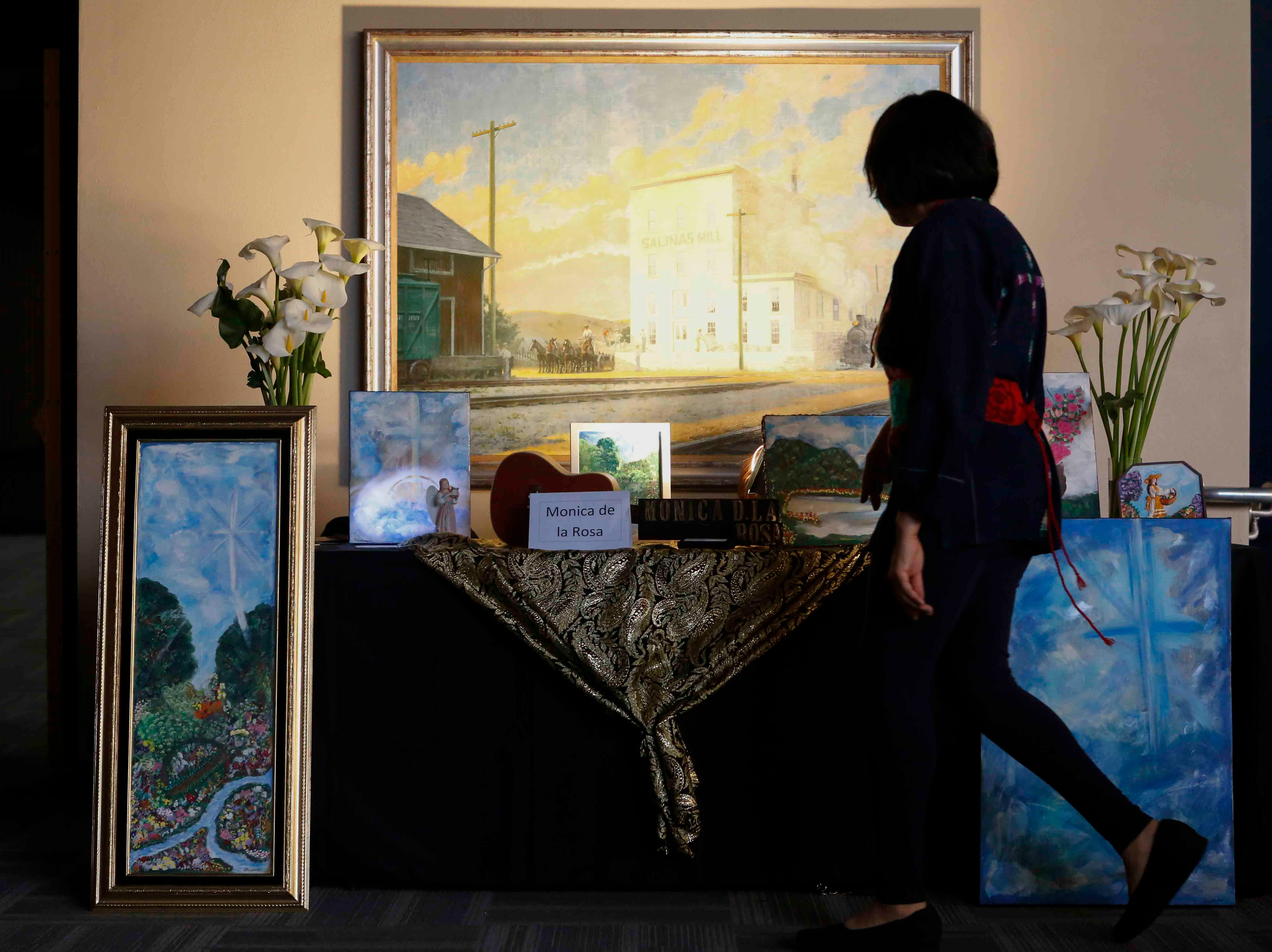 A woman walks past artwork on display during the 12th annual Noche Bohemia at Sherwood Hall on Saturday, April 27, 2019 in Salinas, Calif.