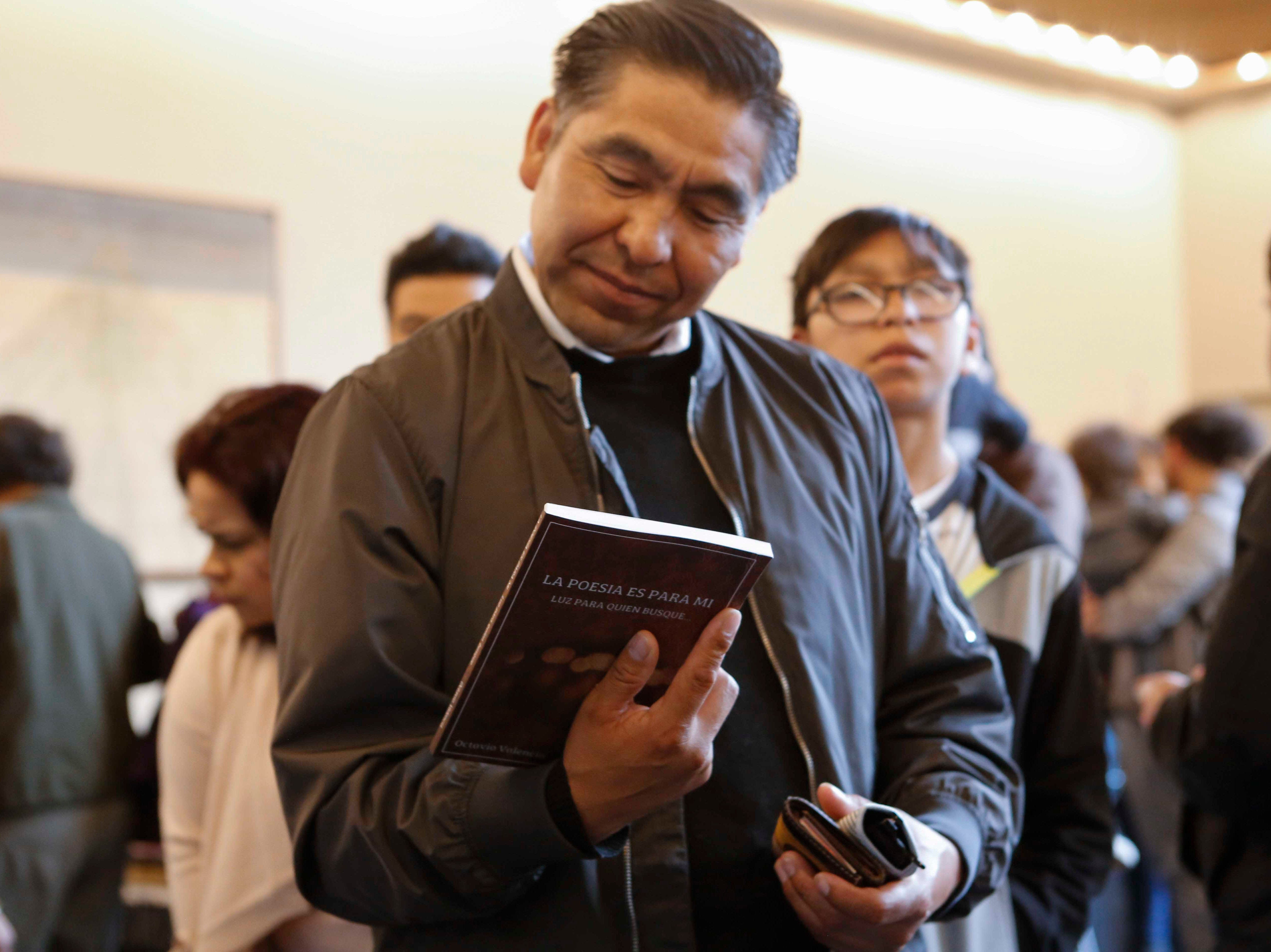 An attendee reads the back of a book during the 12th annual Noche Bohemia at Sherwood Hall on Saturday, April 27, 2019 in Salinas, Calif.