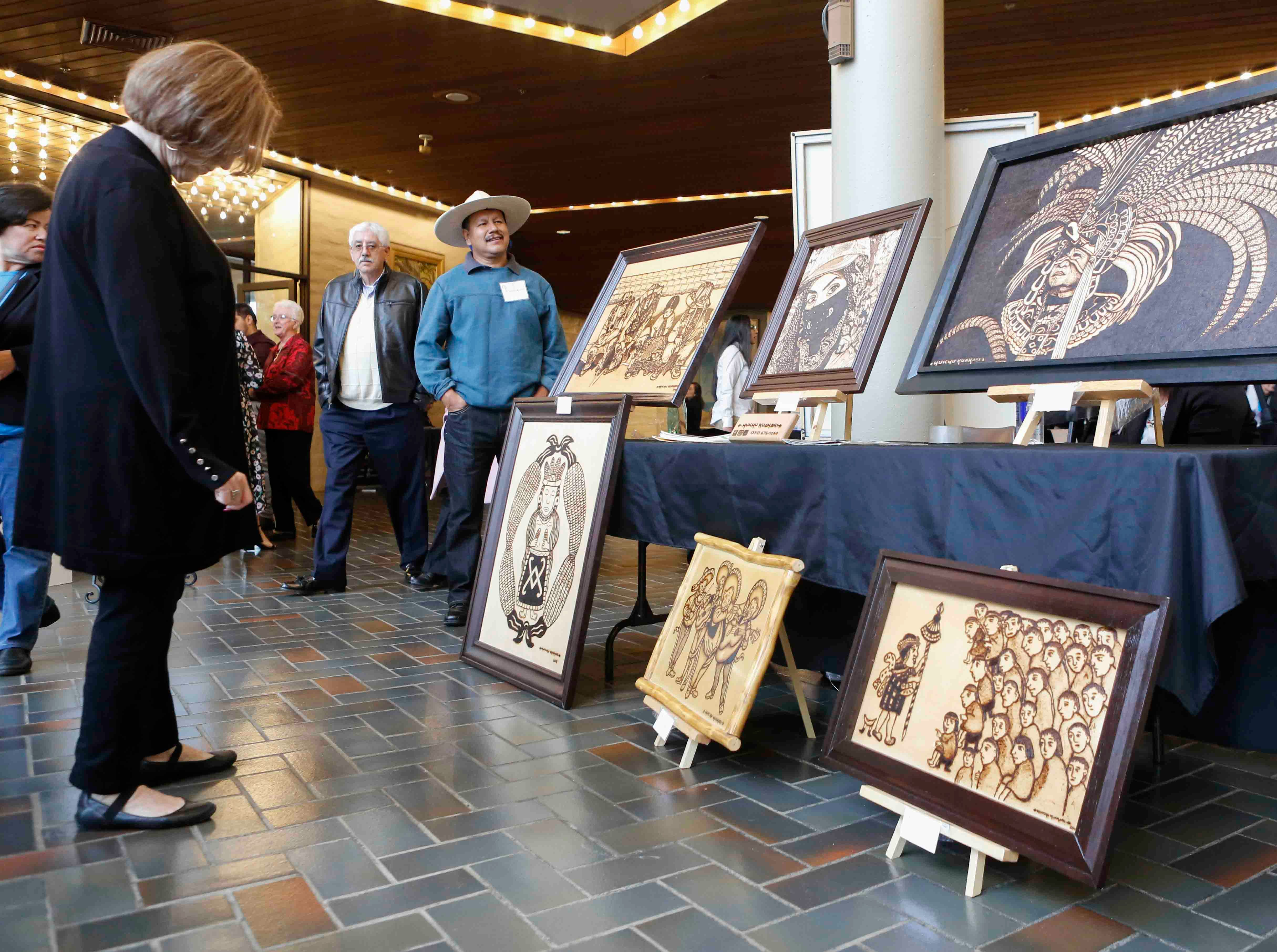 Huichu Huakari of Salinas, center, looks on as attendees gander at his work during the 12th annual Noche Bohemia at Sherwood Hall on Saturday, April 27, 2019 in Salinas, Calif.