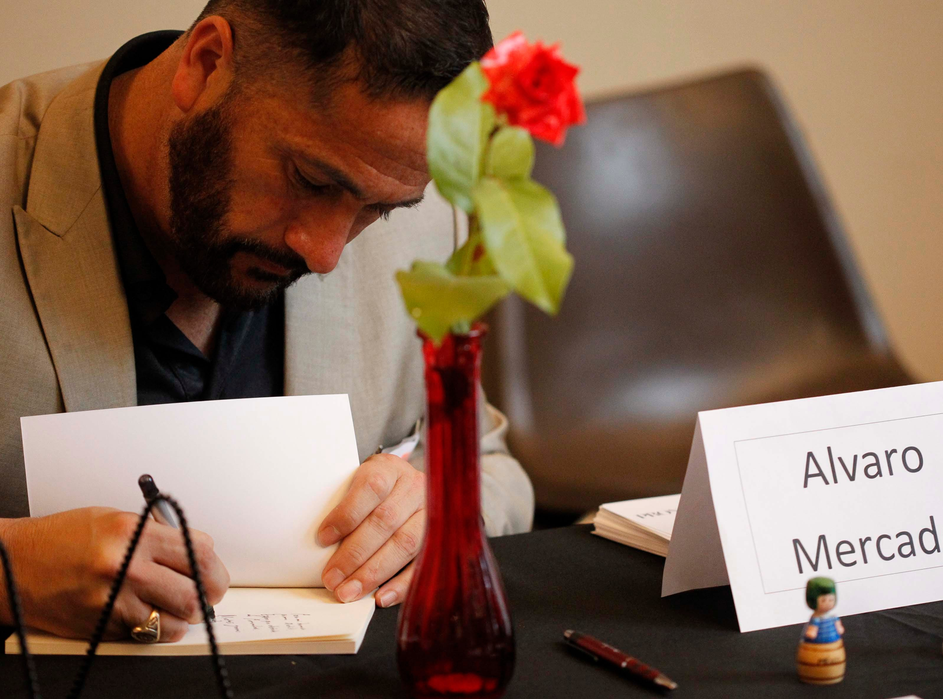 Author Alvaro Mercado of Salinas autographs a book for an attendee during the 12th annual Noche Bohemia at Sherwood Hall on Saturday, April 27, 2019 in Salinas, Calif.