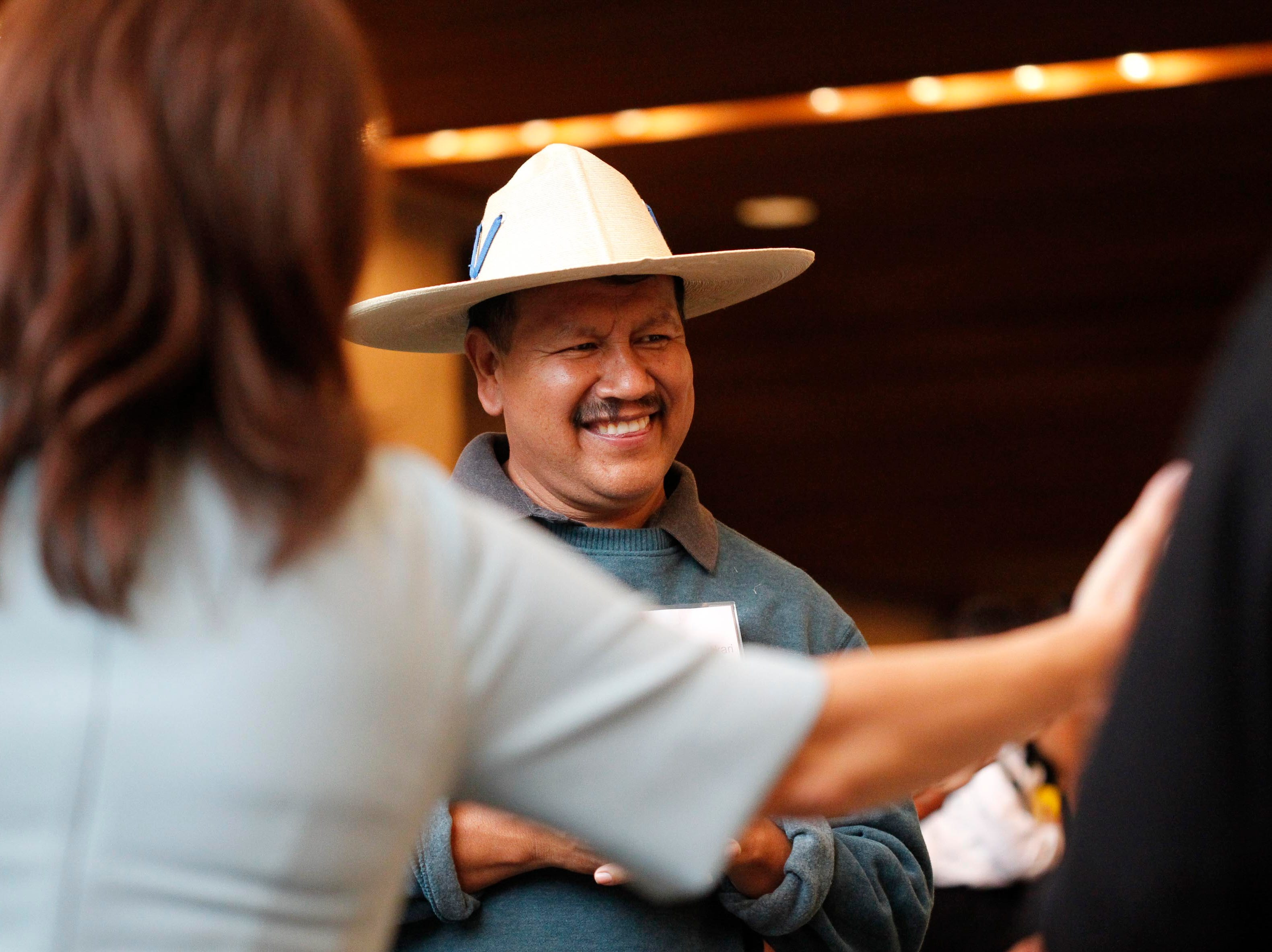 Huichu Huakari of Salinas, center, smiles as he looks on while attendees gander at his work during the 12th annual Noche Bohemia at Sherwood Hall on Saturday, April 27, 2019 in Salinas, Calif.