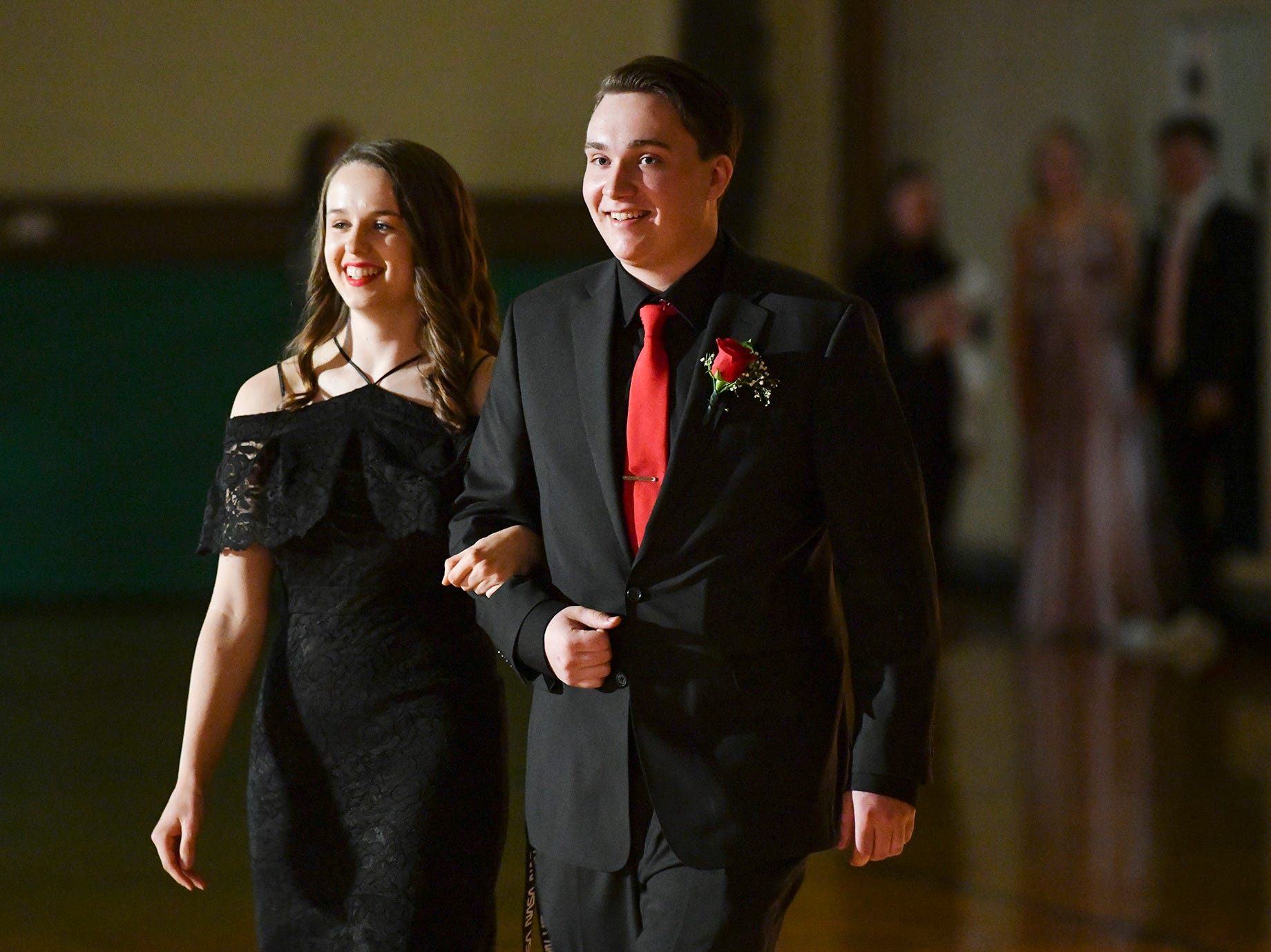 Couples are outlined by the spotlight during prom grand march Saturday, April 27, at Tech High School in St. Cloud.