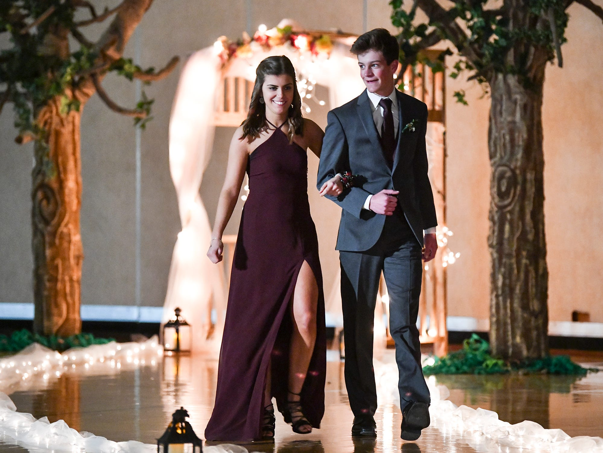 A couple walks down the lighted route during prom grand march Saturday, April 27, at Tech High School in St. Cloud.