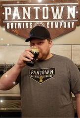 Pantown Brewing Co. head brewer Nick Flies drinks the brewery's Drop Forge Milk Stout, which won third place in the Stouts category of the Minnesota Craft Brewers Guild's first Minnesota Brewers Cup awards Friday, April 26.