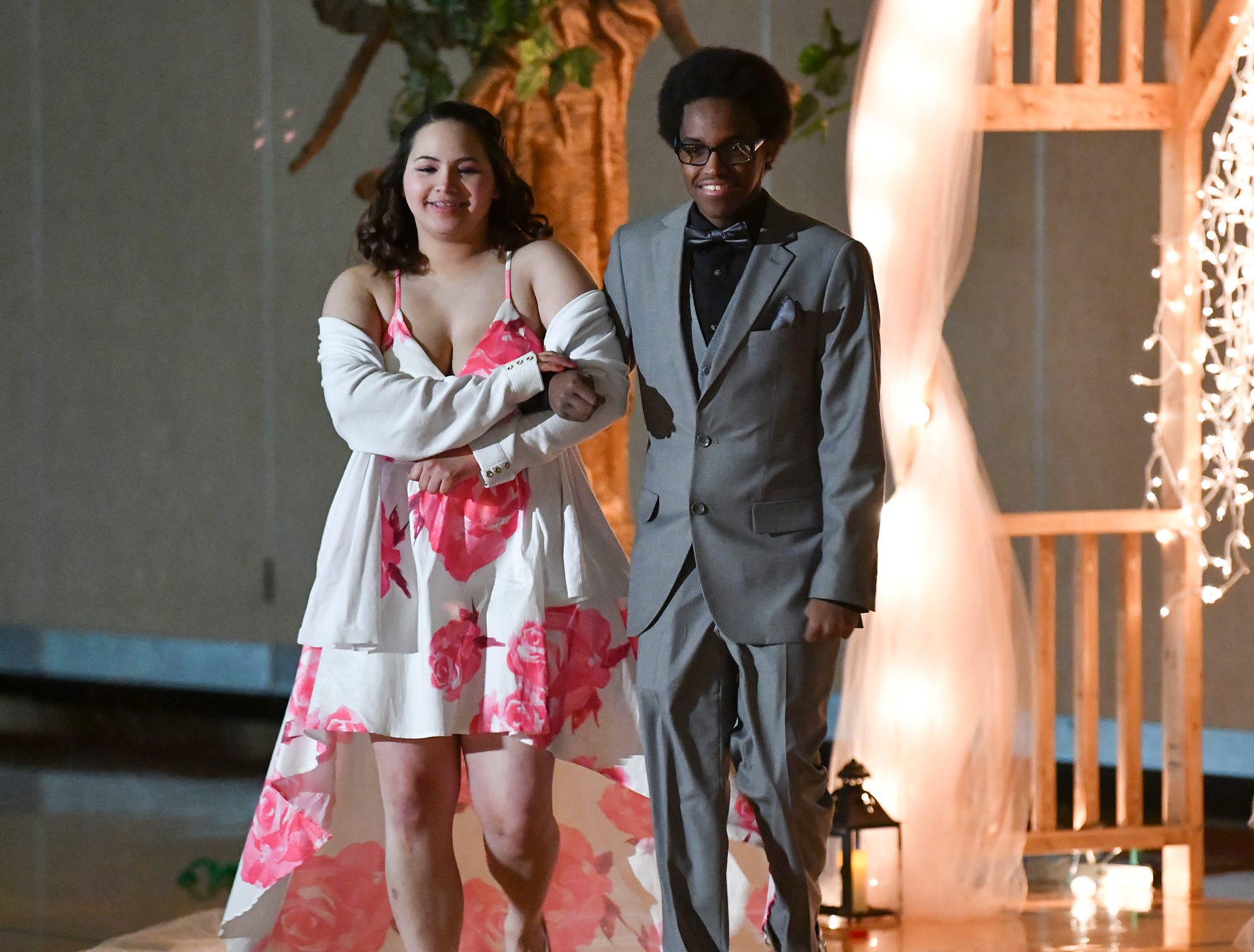 Couples walk down the lighted path during prom grand march Saturday, April 27, at Tech High School in St. Cloud.