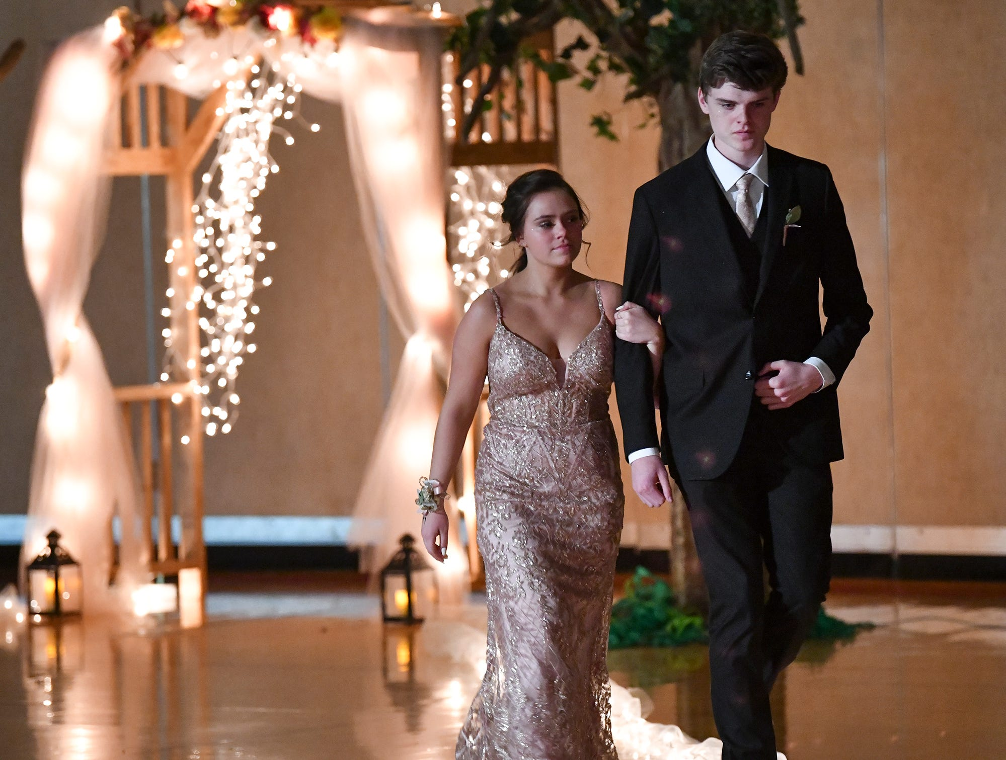 Couples make their way down the lighted path during prom grand march Saturday, April 27, at Tech High School in St. Cloud.