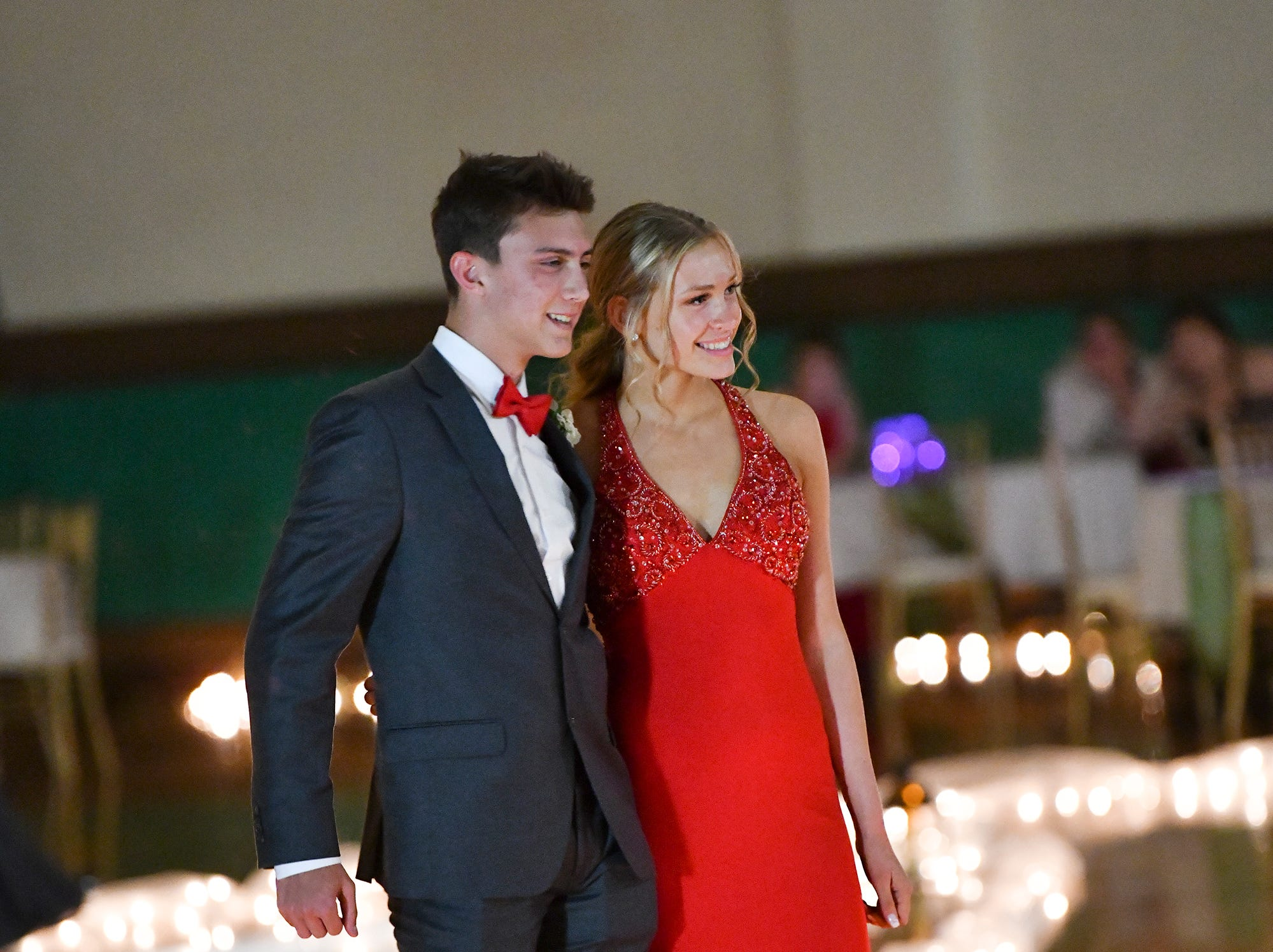 Couples smile for photos during prom grand march Saturday, April 27, at Tech High School in St. Cloud.